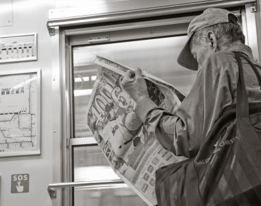 Man reading a newspaper on the subway in Japan