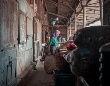 woman standing behind brown wooden cabinet, Legi traditional market