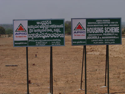 Signboards announcing housing development, as part of the SEZ rehabilitation package. Polepally, Andhra Pradesh.